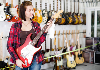 Teenage girl choosing electric guitar