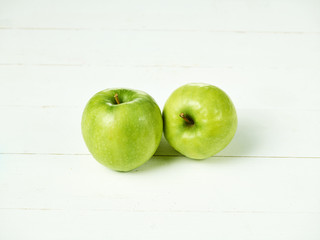 Shot of two fresh green apples with green leaf on a table.