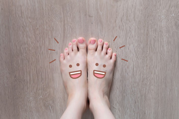 Smiley Face Drawn on Toes. Close Up Female Barefoot On Wooden Floor Background Great for Any Use.