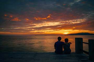 Silhouette of young romantic couple in love is sitting and hugging on wooden pier at the beach in sunrise time with golden sky. Vacation and travel concept. Romantic young couple dating at seaside.