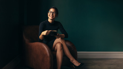 Happy female enjoying coffee while sitting on armchair