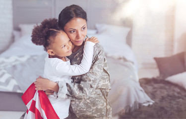 My little girl. Pleasant nice good looking woman wearing a military uniform and holding a US flag while hugging her daughter