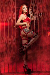 gorgeous girl with red long hair wearing cherry color lingerie with patent leather fetish bdsm harness and erotically poses showing her perfect figure