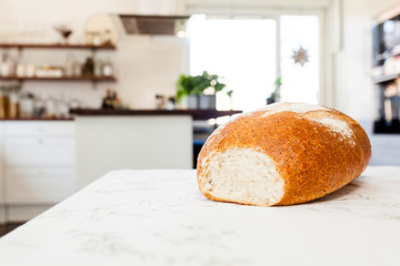 a loaf of bread in the front and kitchen interior unfocused in the background