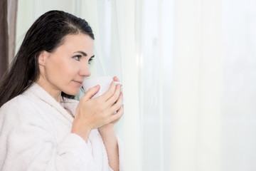 Beautiful woman drinking coffee at a hotel room by the window wearing a white bathrobe