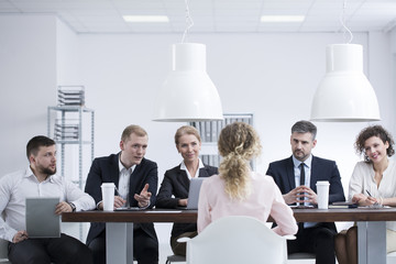 Group of recruiters asking woman