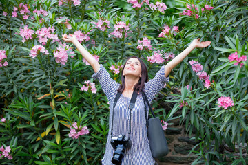 Happy young woman puting hands on the air on flowers background