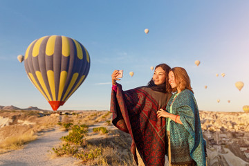 Couple of friends travelers enjoying valley view and making selfie on a phone with wonderful balloons flight over Cappadocia valley in Turkey