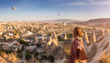 A woman travels through Cappadocia at the background of a grandiose balloon show in Turkey