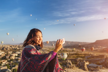Selfie photo of a happy smiling girl in ethnic poncho with hot air ballon flight in Cappadocia