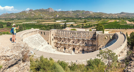 Young tourist woman take a photo of the antique amphitheater Aspendos in Turkey