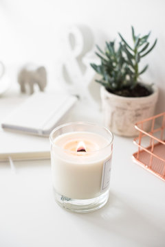 White burning candle on table, home interior decorations