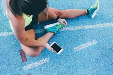 Female athlete using phone to track workout