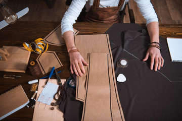 cropped shot of male fashion designer working with sewing patterns, tools and fabric at workplace Wall mural