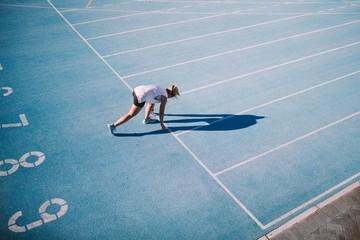 Caucasian female athlete running on blue running track