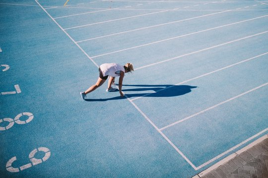 Female athlete takes position on running track