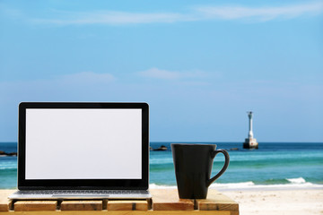 Open the laptop on the beach background.front view with copy space.