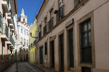 View of a narrow street and buildings with a tower of the Sao Vincente de Fora church on the backrgound, in the historic neighborhood of Alfama in Lisbon, Portugal; Concept for visit Lisbon