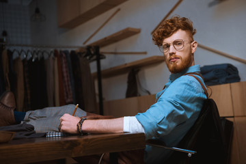 young male fashion designer in eyeglasses looking at camera while taking notes at workplace