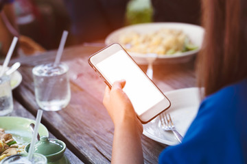 close up of woman hand using or looking at his smartphone and having lunch in the restaurant.