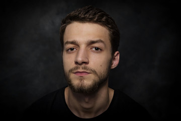 Portrait of a young man with a beard on a dark background.