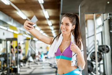 Close up portrait of satisfied happy smiling attractive young active fitness shape girl standing with earphones and towel and taking a selfie in the gym.