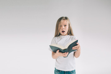 girl in white t-shirt is reading a book on a white background. Child likes to read books