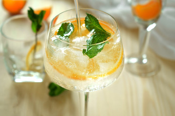 Wineglass is filled up with sparkling cocktail with ice and fruit decorated with mint