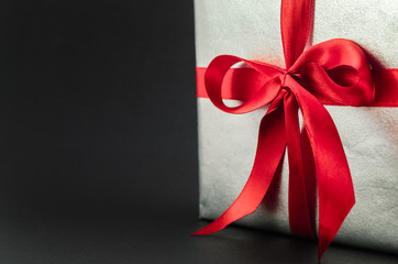 Gift in silver packaging with red ribbon and greetings with Valentine's day. Copyspace