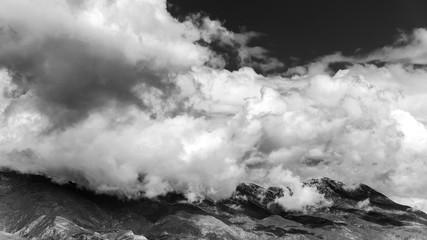 Himmel bedrohliche Wolken vor Gebirge monochrom