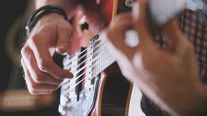 Male musician plays the guitar, hands close up, focus on the guitar fretboard Wall mural