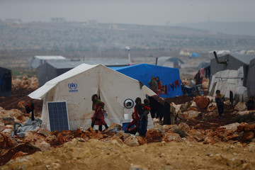 Displaced Syrians stand outside of their tents at Kelbit refugee camp in Idlib province