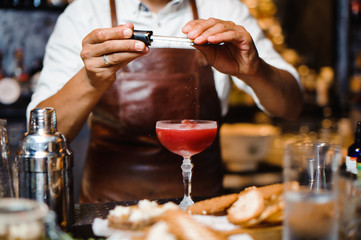Barman in a brown leather apron making fruit alcoholic cocktail