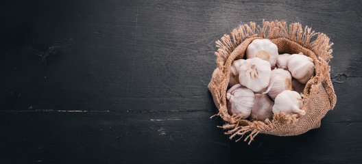 Garlic in a sack of old cloth. Fresh garlic on a wooden background. Top view. Free space for text.