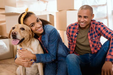 happy african american family with labrador dog moving to new apartment