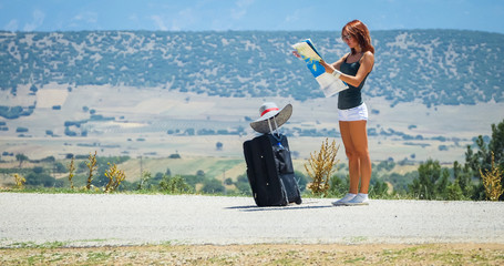 young woman on the road with baggage and map