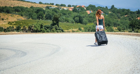 young woman on the road with baggage