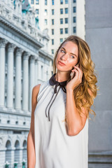 American Business Woman working in New York. Wearing sleeveless white dress, college student with blonde hair standing in front of vintage office building on street, listening, talking on cell phone..