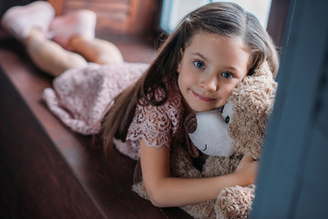 little child embracing teddy bear while lying on windowsill