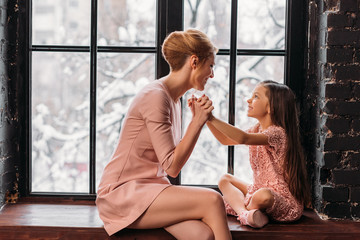 mother and daughter sitting on windowsill and talking