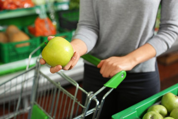 Young woman with fresh ripe apple in supermarket