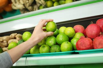 Young woman choosing fresh ripe citrus fruit in supermarket