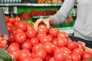 Young woman choosing fresh ripe tomatoes in supermarket