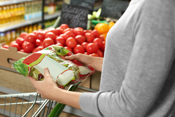 Young woman with fresh lettuce in supermarket