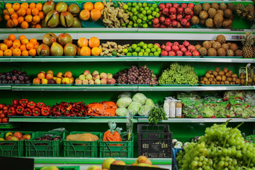 Variety of different fruits and vegetables on shelves in supermarket