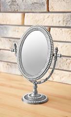 Vintage mirror on wooden table near brick wall