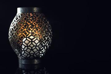 Burning candle in holder on dark background