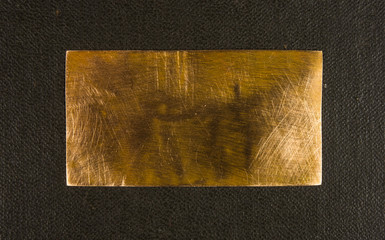 Aged copper plate on black cloth, old worn metal background.