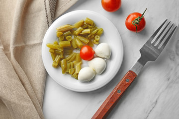 Plate with canned green beans, tomatoes and mozzarella on table