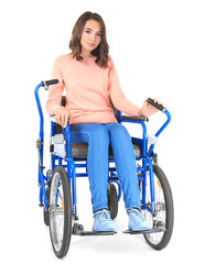 Young woman in blue wheelchair on white background